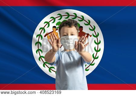Little White Boy In A Protective Mask On The Background Of The Flag Of Belize. Makes A Stop Sign Wit