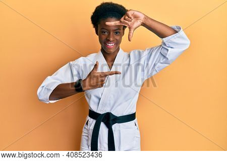Young african american girl wearing karate kimono and black belt smiling making frame with hands and fingers with happy face. creativity and photography concept.