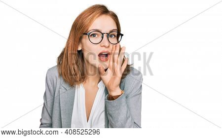 Young caucasian woman wearing business style and glasses hand on mouth telling secret rumor, whispering malicious talk conversation