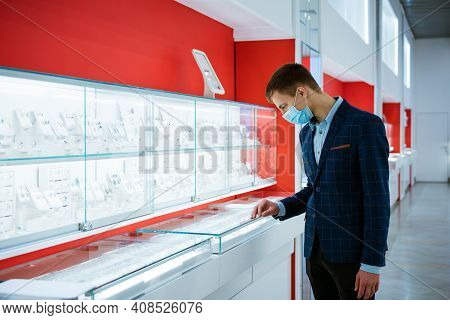 Young Man In A Jewelry Store In A Jacket And A Medical Mask Chooses Jewelry