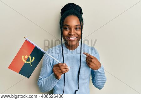 African american woman with braided hair holding angola flag smiling happy pointing with hand and finger