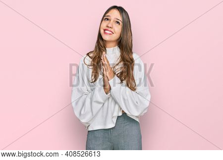Young brunette woman wearing casual turtleneck sweater begging and praying with hands together with hope expression on face very emotional and worried. begging.