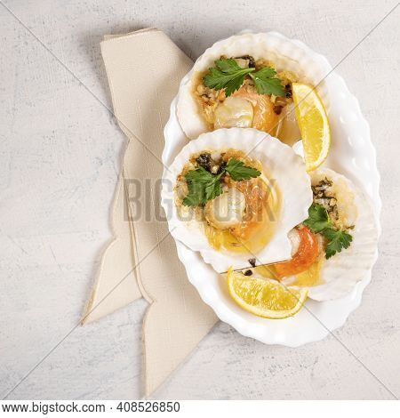 Baked Scallops With Caviar And Creamy Garlic Sauce In White Plate. Scallops With Lemon On White Back
