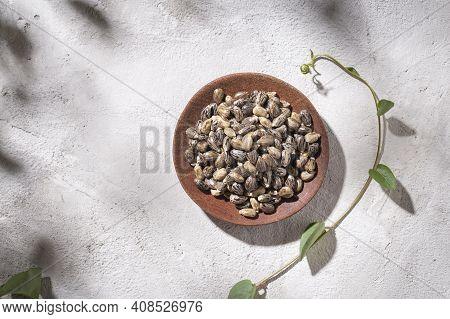 Grains Of Castor Oil Plant, In Bowl On White Background