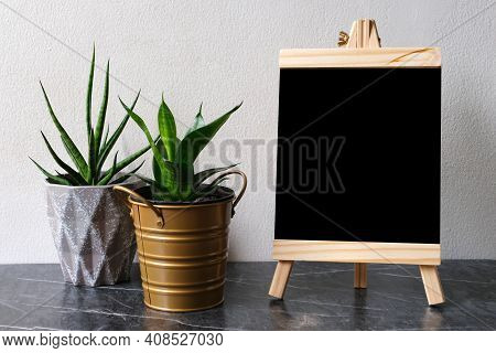 Blank Black Wooden Board, Chalkboard, Standing Over White Cement Wall With Copy Space, Template, Bla