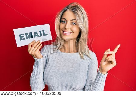 Beautiful blonde woman holding paper with email address smiling happy pointing with hand and finger to the side