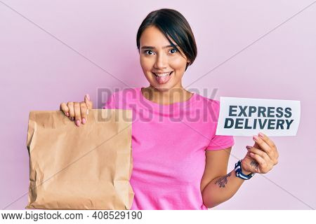 Beautiful young woman with short hair holding paper pag with express delivery text sticking tongue out happy with funny expression.