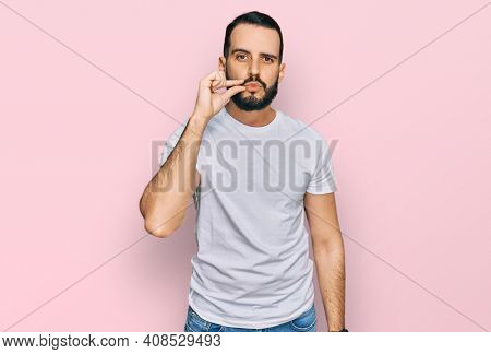 Young man with beard wearing casual white t shirt mouth and lips shut as zip with fingers. secret and silent, taboo talking