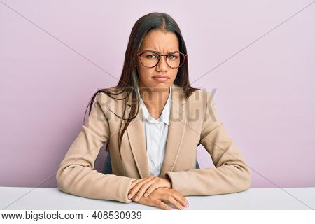 Beautiful hispanic woman working at the office skeptic and nervous, frowning upset because of problem. negative person.