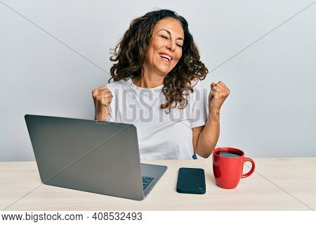 Beautiful middle age woman working at the office using computer laptop very happy and excited doing winner gesture with arms raised, smiling and screaming for success. celebration concept.