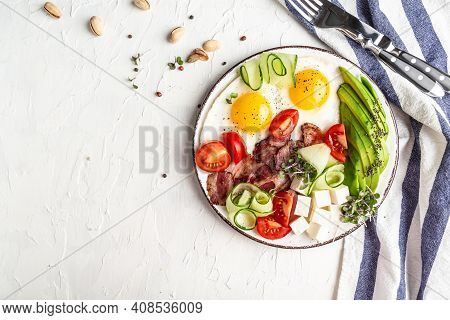Plate With A Keto Diet Food. Paleo Keto Breakfast Fried Eggs, Bacon, Avocado, Cheese And Fresh Salad