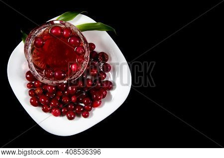 Cranberries On White Plate And Cranberry Juice In Cup Isolated On Black Background.