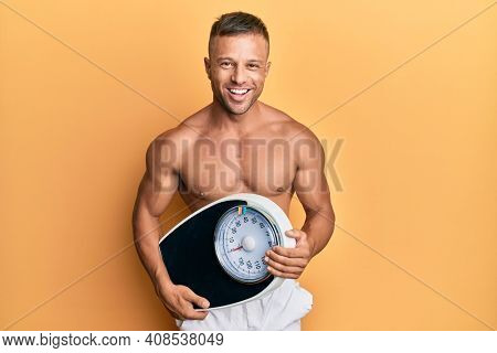 Handsome muscle man holding weight machine to balance weight loss smiling and laughing hard out loud because funny crazy joke.