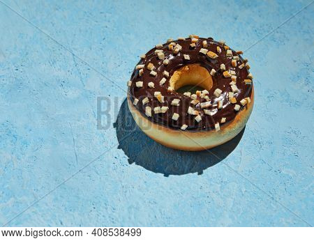 Donut With Chocolate Frosting And Sprinkles On Blue Background