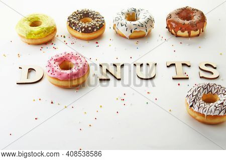 Multi Colored Donuts With Icing, Sprinkles And The Inscription Donuts On White Background