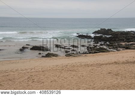 Waves Breaking In The Shallows Into Black Rocks On Shoreline