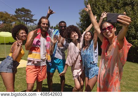 Diverse group of friends taking selfie at a pool party. Hanging out and relaxing outdoors in summer.