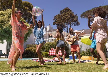Diverse group of friends dancing and smiling at a pool party. Hanging out and relaxing outdoors in summer.