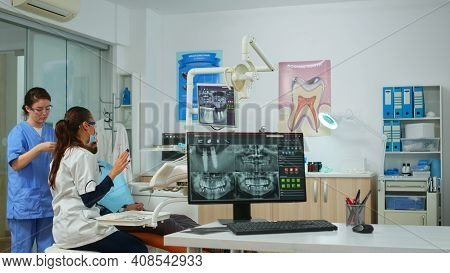 Dental Doctor Pointing On Digital Screen Showing Dental Implants, Preparing Man For Surgery. Dentist