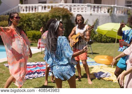 Diverse group of friends having fun and dancing at a pool party. Hanging out and relaxing outdoors in summer.