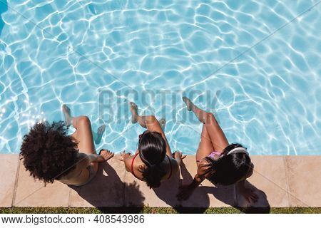 Diverse group of female friends sitting at the poolside. hanging out and relaxing outdoors in summer.