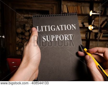 Lawyer Reads About Litigation Support And Holds Pen.
