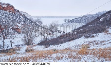 winter scenery of mountain lake at foothills of Rocky Mountains, frozen Horsetooth Reservoir as seen from Lory State Park  in northern Colorado