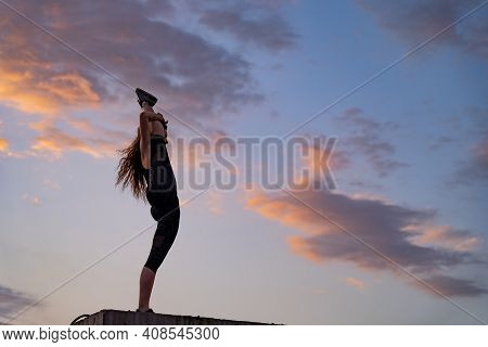 Flexible Female Dancer On The Edge Of Rooftop On The Dramatic Sky Background During Sunset . Concept