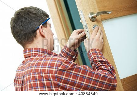 Male handyman carpenter at interior wood door lock installation