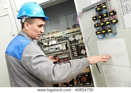 One electrician builder at work checking wire with drawing inspecting high voltage power electric line distribution fuseboard