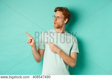 Impressed Redhead Man In Glasses And T-shirt, Pointing Fingers And Looking Left At Promo Offer, Star