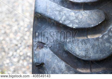 Heavy Machinery Wheel Closeup. Rustic Machine Tire. Heavy Truck Rim On Bumpy Road Backdrop. Road Con
