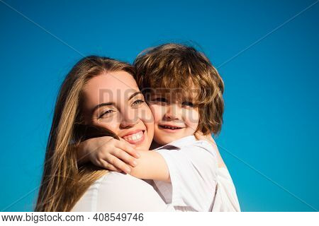 Happy Family Outdoors. Motherhood. Son Embrace Mother. Young Smiling Family With Child. Kids Love An