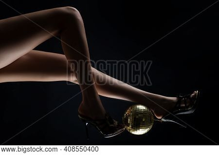 Party Legs. Disco Event. Woman Heels With Gold Disco Ball. Celebrate Concept. Gold Disco Ball On Hig