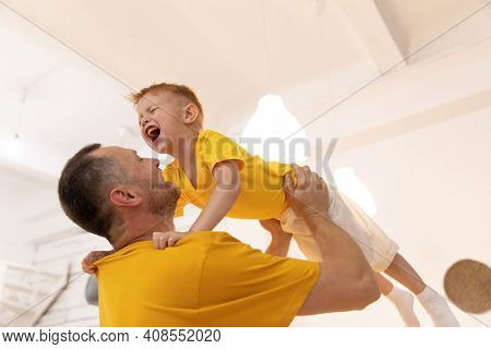 Dad And Son In Yellow T-shirts. Father Raises A Small Child In His Arms