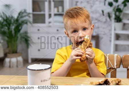 Young Boy With Chocolate On His Face. Little Red Boy Eats A Croissant With Chocolate. Boy Dirty His