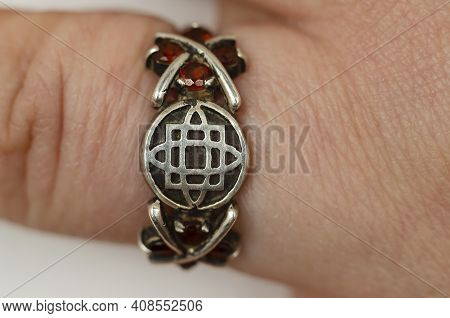 Closeup Of A Silver Ring On The Finger Of An Adult Caucasian Woman. Slavic Symbol Of The Goddess Fre