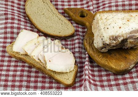 Traditional Ukrainian Food. Salted Lard, Rye Bread And A Wooden Cutting Board On A Red Checkered Clo