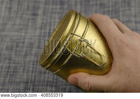 A Man's Hand Holding A Tea Coffee Tin With A Clasp Close-up. Gold Latch Lock Tin For Dry Goods. Sele