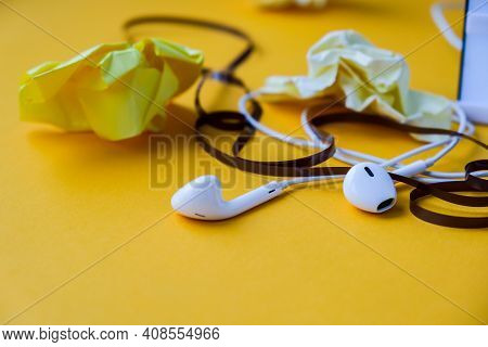 Hedphones With Audio Cassette Tape And Crumpled Paper On Yellow Background, Copy Space. Podcast Epis