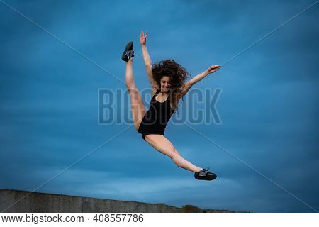 Super Flexible Woman Jumping On The Sky Background. Concept Of Healthy Lifestyle, Happiness And Joy