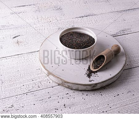 Uncooked Black Raw Quinoa Seeds In White Bowl And Sccop On Board And On White Wooden Table. Few Seed