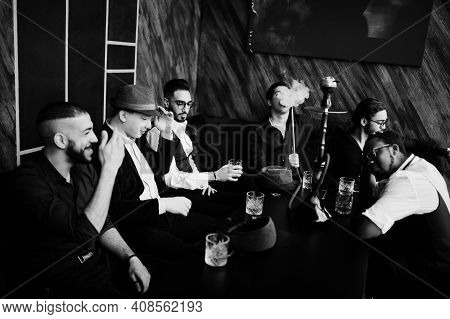 Group Of Handsome Retro Well-dressed Man Gangsters Spend Time At Club, Smoking Hookah. Multiethnic M