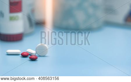 Round White Tablets And Blurred Red And White Tablets Pills. Pills On Blurred Pills Plastic Bottle.