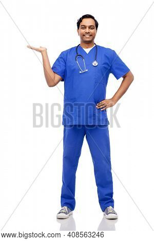 healthcare, profession and medicine concept - happy smiling indian doctor or male nurse in blue uniform with stethoscope holding something imaginary on empty hand over white background