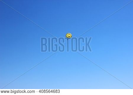 Silhouette Of A Parachutist In Flight Under A Yellow Parachute Against The Blue Sky. Copy Space. Fly