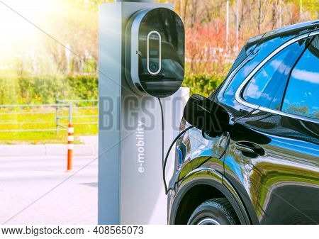 Refueling For Cars E-mobility. Charging An Electric Car At Hybrid Engine Gasoline And Electricity. S