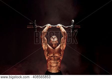 Portrait Of Muscular Man Lifting Dumbbell In Red Smoke. Studio Shot. Exercise For Triceps. Motivatio