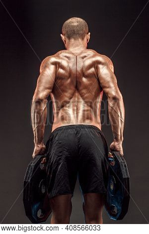 Muscled Shirtless Male Model Showing His Back Muscles On Dark Background Isolate.