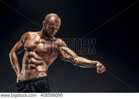 Strong Man With Perfect Abs, Shoulders, Biceps, Triceps And Chest. Bodybuilder Topless Flexing His M